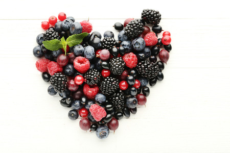 Berries in heart shape on white wooden table
