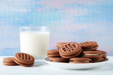 Chocolate cookies with glass of milk on wooden table