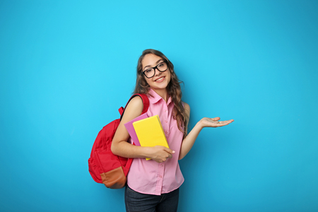 Portrait of student girl with backpack and books on blue background Stock fotó