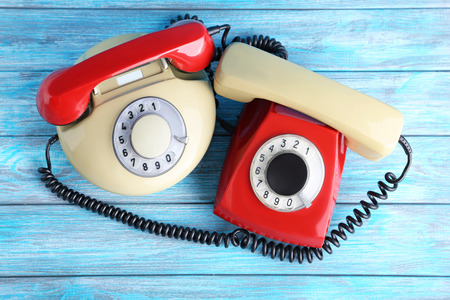 Red and beige retro telephones on blue wooden table