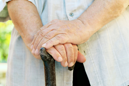 puckered: Hands of old senior with walking stick