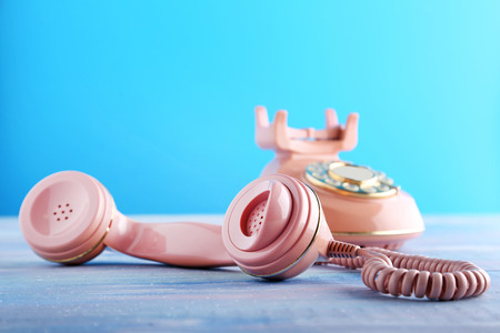 shiny buttons: Pink retro telephone on blue wooden table Stock Photo