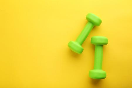 黄色の背景に緑のダンベル 写真素材