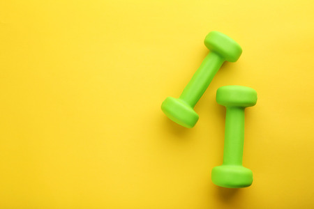 Green dumbbells on yellow background