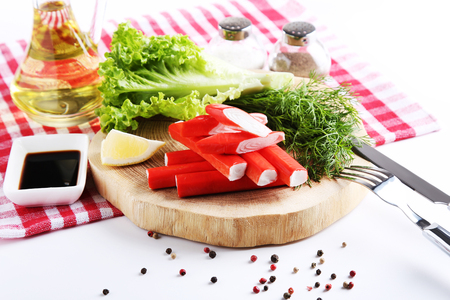 Crab sticks with lettuce and dill on brown wooden cutting board