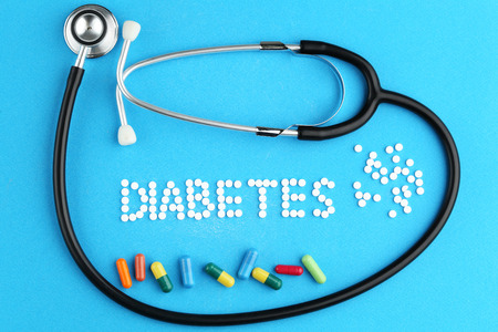 Sweetener tablets with stethoscope and capsules on blue background