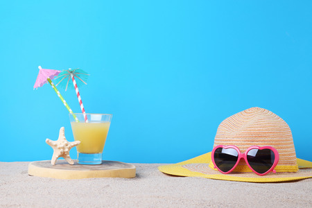 Sunglasses with hat and glass of juice on the beach sand