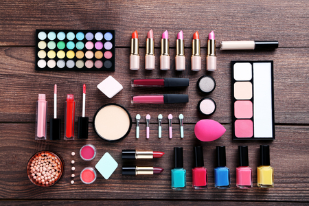 gloss: Different makeup cosmetics on brown wooden table
