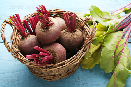 Fresh and ripe beets in basket on blue wooden table