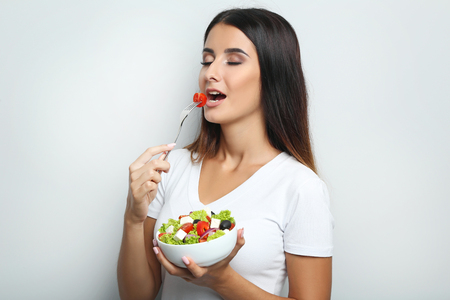 olive green: Young woman with vegetable salad in bowl on grey background Stock Photo
