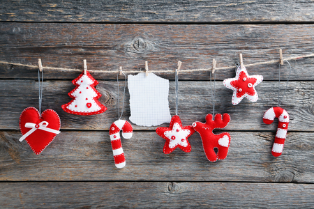 sheet: Christmas decorations hanging with blank sheet of paper on rope on wooden background Stock Photo