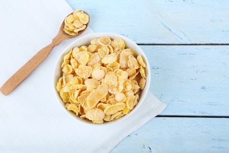 Cornflakes in bowl on blue wooden table Stok Fotoğraf