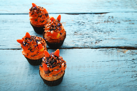 Halloween cupcakes with sprinkles and candies on blue wooden table Stock Photo