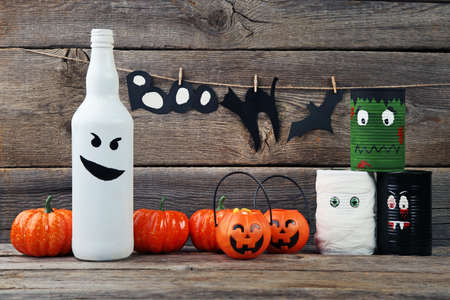 Halloween monsters with pumpkins on grey wooden table Stock Photo