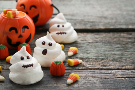 Halloween meringue with candies on grey wooden table