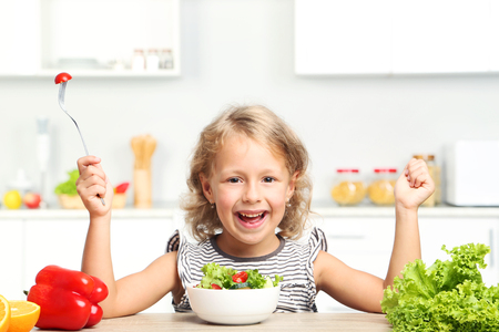 Little girl eating salad in the kitchen