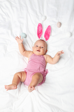 Little newborn baby with rabbit ears on white bed Stock Photo