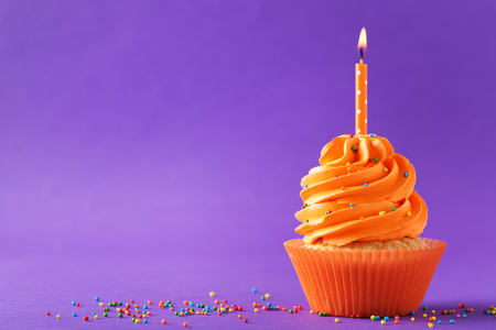 Tasty cupcakes with candle on a purple background 스톡 콘텐츠