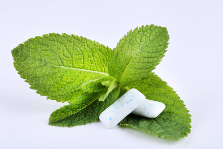 Chewing gums with mint leafs on white background