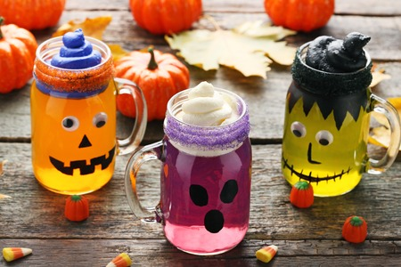 Halloween jelly in glass jars with candies on wooden table