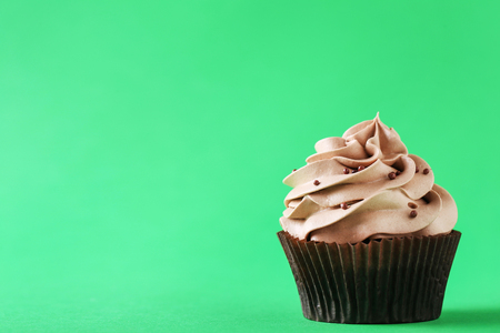 Tasty cupcake on a green background