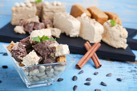 Tasty slices of halva in bowl with cinnamon on wooden table
