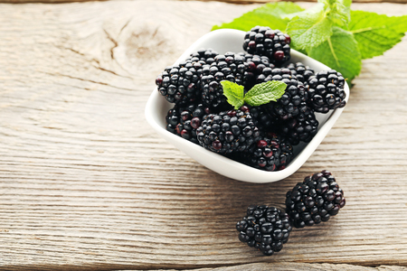 Ripe and sweet blackberries in bowl on wooden table Banco de Imagens