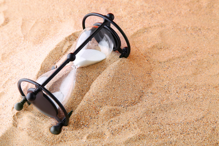 clock: Black hourglass on the beach sand
