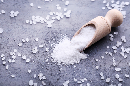 White sea salt in scoop on grey wooden table