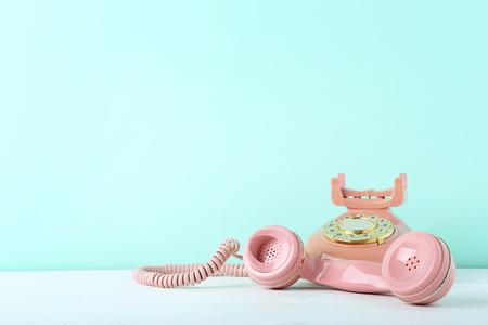 Telefono retrò rosa su tavola di legno bianco