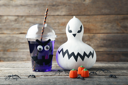 Halloween cocktail in plastic cup with pumpkin on grey wooden table Stock Photo