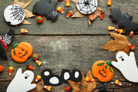 Halloween gingerbread cookies and candies on wooden table Stock Photo