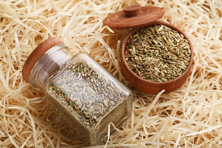 Fennel seeds in glass jar and wooden bowl on raffia background