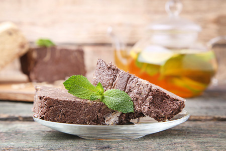 Tasty halva with cocoa and mint leaf on wooden table