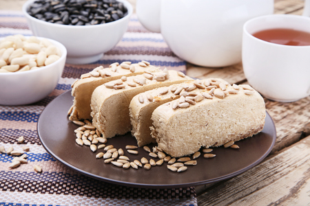 Tasty slices of halva in plate on wooden table