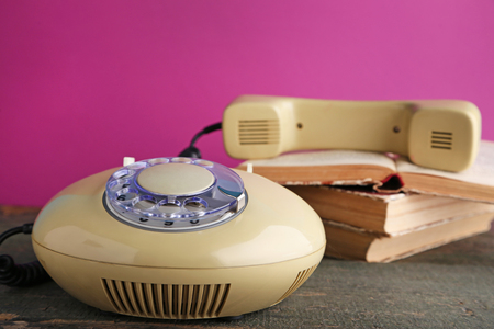 Beige retro telephone with books on grey wooden table Stock Photo