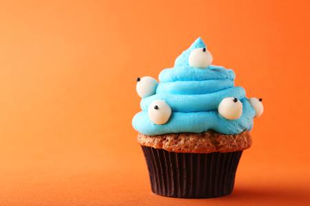 Halloween cupcake on orange background