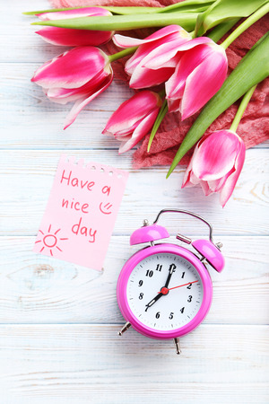 bouquet of pink tulips with alarm clock and sheet of paper on