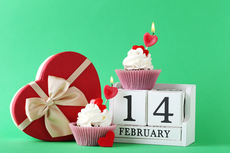 Tasty cupcakes with cube calendar on green background Stock Photo