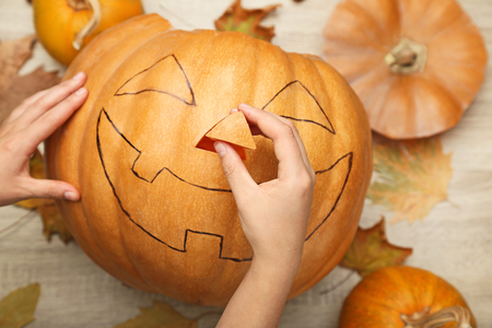 Halloween pumpkin with dry leafs on wooden table