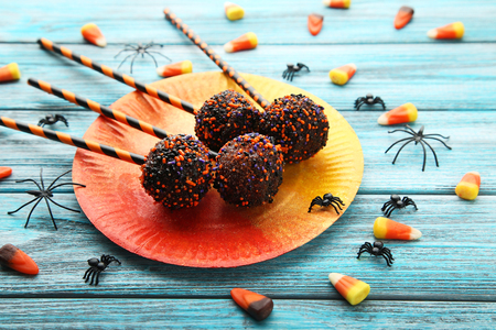 Sweet halloween cake pops with candies on blue wooden table Stock Photo
