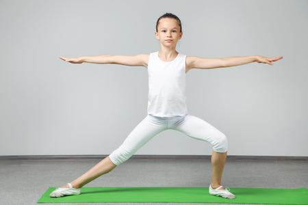 Young girl doing exercises on green yoga mat