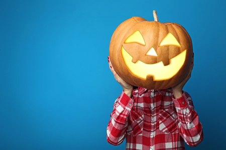 Female hands holding halloween pumpkin on blue background Stock Photo