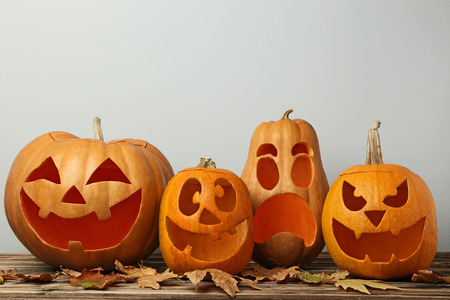 Halloween pumpkins with dry leafs on brown wooden table