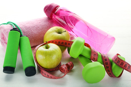 Measuring tape with green apples, dumbbells, bottle of water and skipping rope