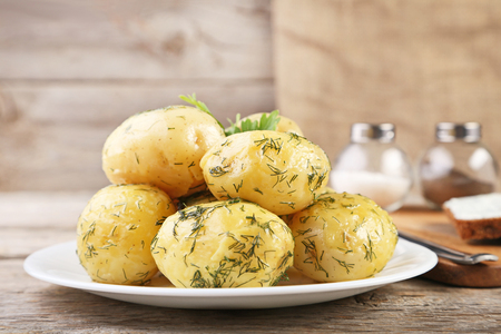 Boiled potatoes in plate on wooden table