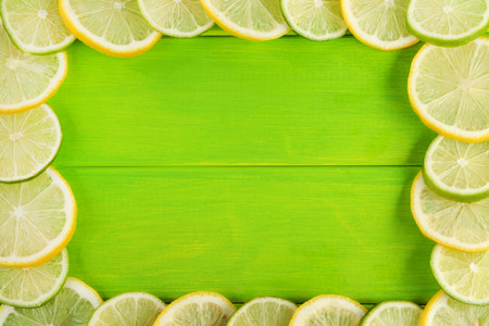 Frame of limes and lemons on green wooden table Stock Photo