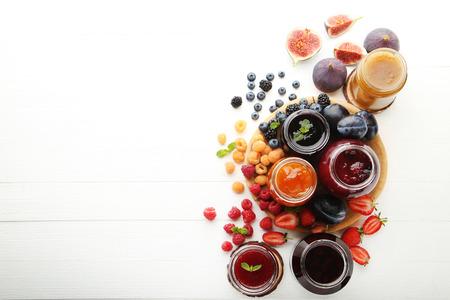 나무 테이블에 잼 및 열매의 다른 종류와 유리 항아리