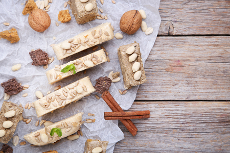 Tasty slices of halva with walnut and cinnamon on grey wooden table Stock Photo