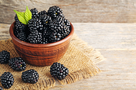 Ripe blackberries in bowl on wooden table